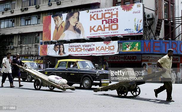 Local taxis and hand cart pullers pass in front of a billboard advertising Bollywood movie directed by Rohan Sippy 'Kuch Na Kaho' showing pictures of...