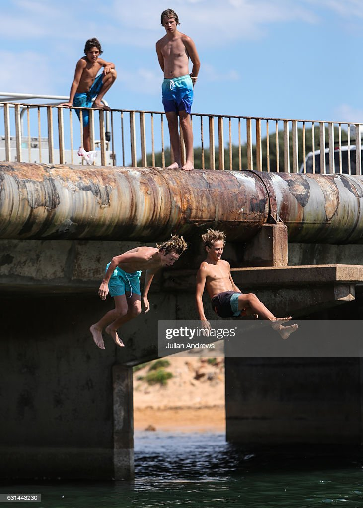 Local teenagers jumping into Narrabeen Lagoon from the road bridge on January 11, 2017 in Sydney, Australia. High temperatures combined with rising humidity have made for an uncomfortable day in Sydney, with temperatures hitting 40 degrees Celsius in some parts.