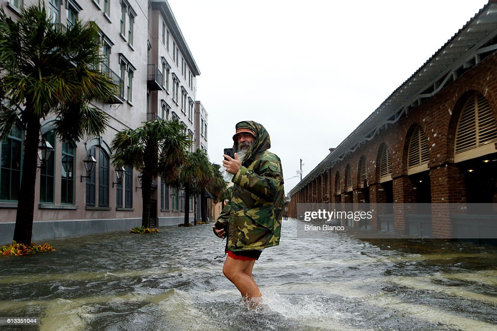 Local tour guide Larry Gerald live streams himself on social media as he crosses flooded S. Market Street at East Bay St. in the wake of Hurricane Matthew on October 8, 2016 in Charleston, South Carolina. Across the Southeast, Over 1.4 million people have lost power due to Hurricane Matthew which has been downgraded to a category 1 hurricane on Saturday morning.