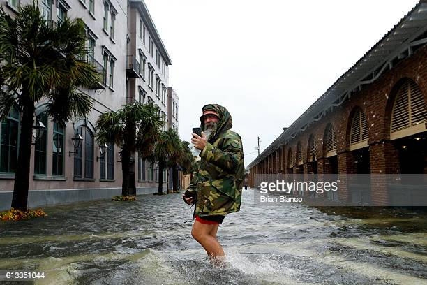 Local tour guide Larry Gerald live streams himself on social media as he crosses flooded S Market Street at East Bay St in the wake of Hurricane...