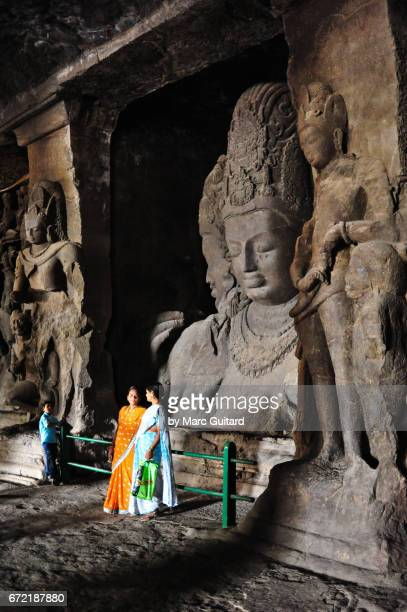 Local tourists posing in front a huge sculpture of Trimurti Elephanta Caves, Mumbai, Maharashtra, India