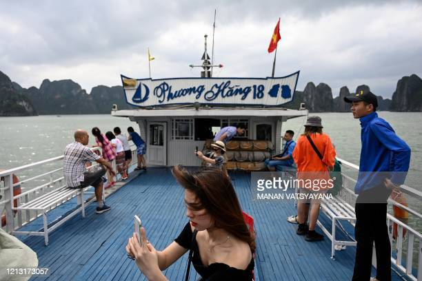 Local tourists take photographs on a boat in the midst of Ha Long Bay in northeastern province of Quang Ninh on May 16 2020