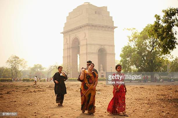 Local tourists walk in front of India Gate on March 18 2010 in Delhi India The memorial was erected to honour Indian soldiers who lost their lives in...