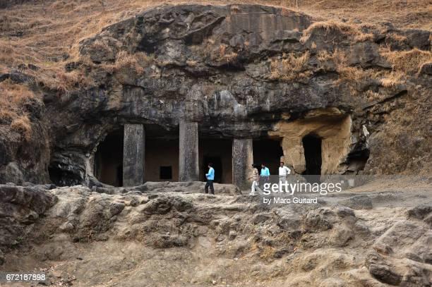 Local tourists walking in front of an entryway to the Elephanta Caves, Mumbai, Maharashtra, India