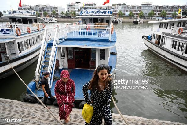 Local tourists wearing face masks disembark following a boat ride in the waters of Ha Long Bay in northeastern province of Quang Ninh on May 16, 2020.