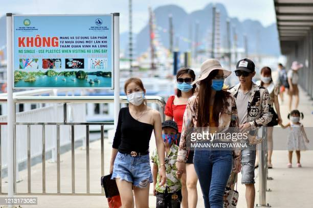 Local tourists wearing face masks leave a pier after returning from a cruise trip in the waters of Ha Long Bay in northeastern province of Quang Ninh...
