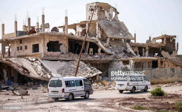 Local transport microbuses are seen driving past destroyed buildings in an opposition-held neighbourhood of the southern Syrian city of Daraa on...