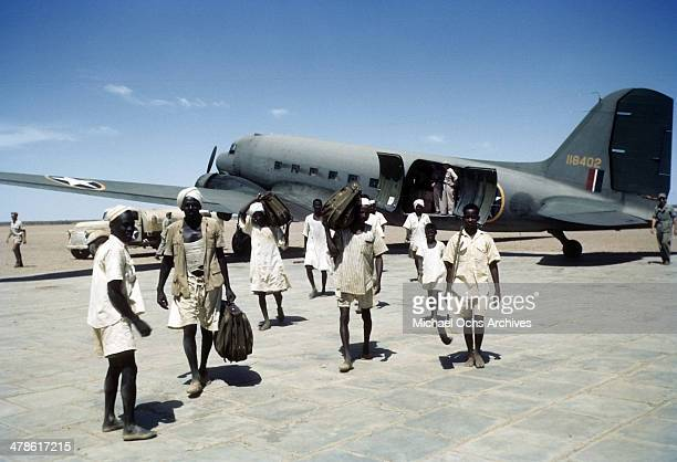 Local tribesmen carry bags off a C47 Skytrain plane on the Wadi Seidna runway at the US Army Air Force/Royal Air Force base in Khartoum AngloEgyptian...