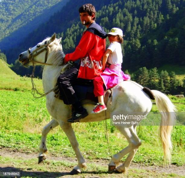 Local Tusheti boy from Cesho takes a ride on a white horse with his younger sister. Georgia Kakheti Tusheti Caucasus