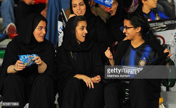 Local United Arab Emirates girl football fans act shocked as one of their friends shows off an Inter Milan shirt underneath her Abaya black Islamic...