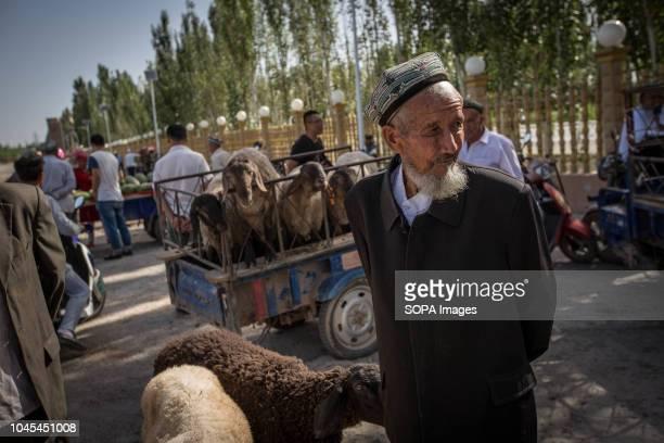 MARKET KASHGAR XINJIANG CHINA A local Uyghur man waits for customers at a livestock market in Kashgar city northwestern Xinjiang Uyghur Autonomous...