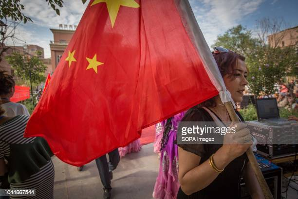 TOWN KASHGAR XINJIANG CHINA A local Uyghur woman seen holding a Chinese flag during the traditional Uyghur dancing performance in the Kashgar old...