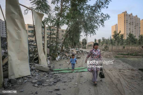 A local Uyghur woman seen walking with her kid through the rubble of a demolished house to give space for new home in the city of Hotan in the...