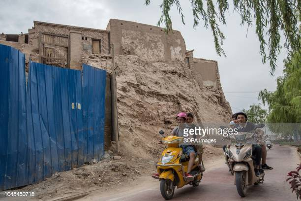 Local Uyghur workers seen driving Chinese branded electric motorcycle next to rubbles of traditional houses set to be completely demolish to make way...