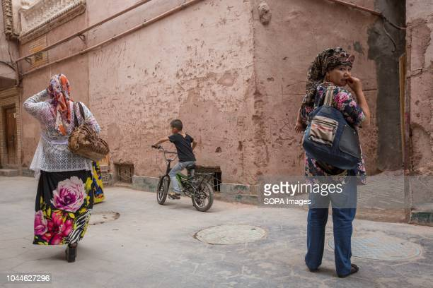 TOWN KASHGAR XINJIANG CHINA Local Uyghurs are pictured walking on the street of the Kashgar old Town in Kashgar city northwestern Xinjiang Uyghur...