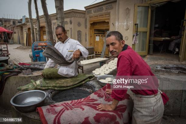 Local Uyghurs seen cooking traditional bread on the streets of Keriya in the Hotan Prefecture Xinjiang Uyghur Autonomous Region in China Kashgar is...