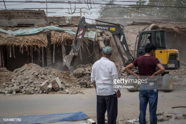 Local Uyghurs seen looking at a backhoe loader destroying traditional homes to build newly houses in the streets of Keriya in the Hotan Prefecture...