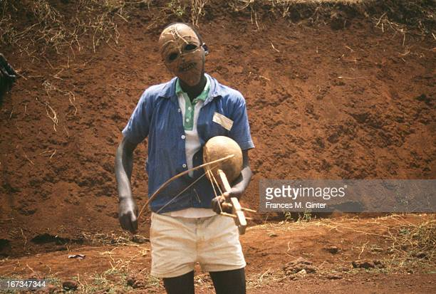 A local village boy plays music on the side of the road from Arusha to Gibbs Farm Tanzania December 1991