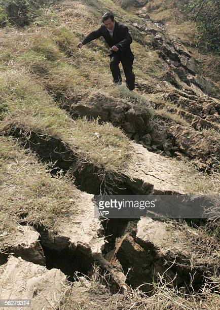 A local villager climbs over large cracks in the ground after a large section of farmland dropped four metres after a 57 earthquake hit 26 November...