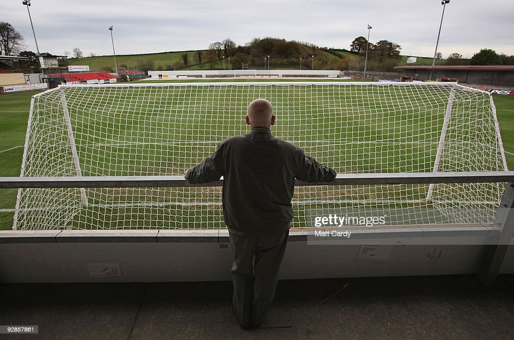 A local villager looks out at the pitch from behind a goal net at Paulton Rovers Football Club on November 6, 2009 in Paulton, England. Non-league Paulton Rovers are currently preparing for the single biggest day in their 128-year history as they face Norwich City in the FA Cup first round tomorrow. The Somerset village club, which beat Chippenham Town before being drawn against the League One club, normally has an attendance of 200, but will see capacity at the ground swell to 2500 and the match broadcasted live on television to an estimated audience of 2 million.