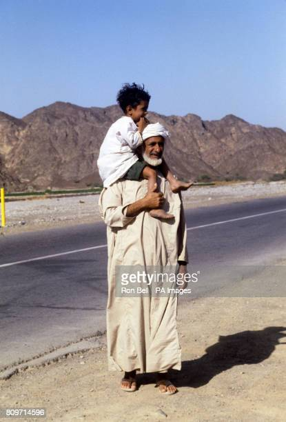 A local villager with his son on the road from Nizwar to Muscat Oman