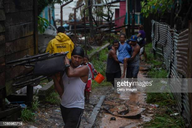 Local villagers carry a woman during an evacuation ahead of landfall of Hurricane Iota on November 16, 2020 in Puerto Cabezas, Nicaragua. Less than...