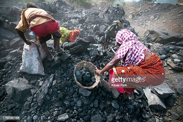 CONTENT] Local villagers carry coal after having scavenged the coal illegally from an open cast coal mine in the village of Jina Gora near Jharia...