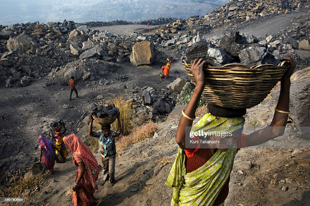 Local villagers carry scavenged coal from an open-cast coal mine in Dhanbad, Jharkhand, India on December 5, 2014, tying to earn a few dollars a day. Indian government lead by Prime Minister Narendra Modi plans to double its coal production by 2019.