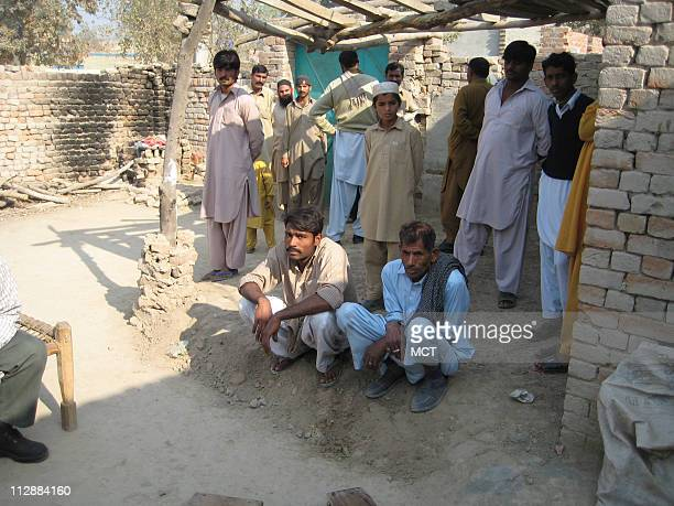 Local villagers gather in the courtyard of Ajmal Ameer Kasab's family home in Faridkot village near Depalpur in Pakistan