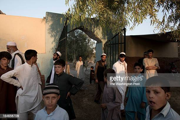 Local villagers leave through the gate of the Mia Ali Sahib shrine outside Jalalabad Afghanistan on October 19 2012 Relatives bring those with a...