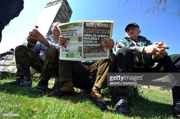 Local villagers read todays newspaper with the headline reading The worst crime in the history of Serbia in the village of Velika Ivanca 40...