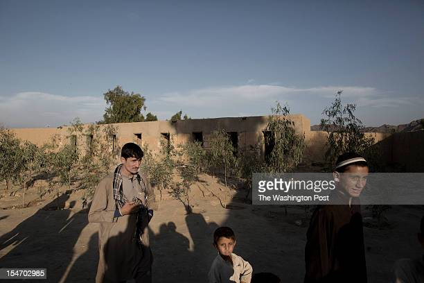 Local villagers walk in the yard of the Mia Ali Sahib shrine beside the cells for people suffering from a mental illness outside Jalalabad...