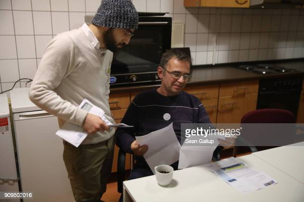 Local volunteer Goeran Havenstein helps Syrian refugee Mohammad Ezziddin to figure out a letter Mohammad received in the mail during a weekly...