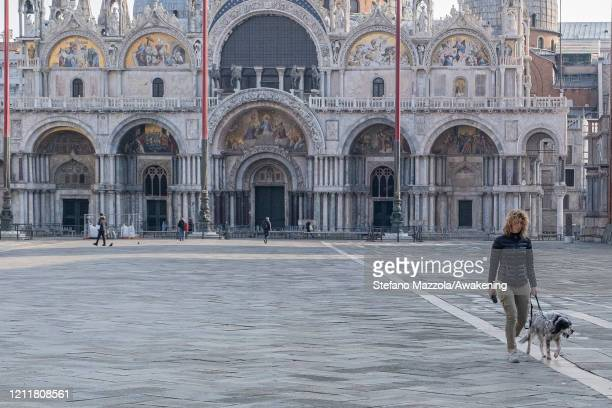 Local walks in an empty Piazza San Marco with the dog on March 11 2020 A local walks near the Grand Canal with a protective face mask in Venice Italy...
