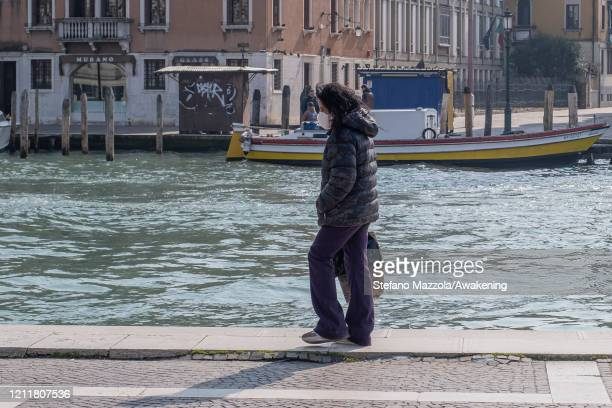 A local walks near the Grand Canal with a protective face mask on March 11 2020 in Venice Italy The Italian Government has taken the unprecedented...