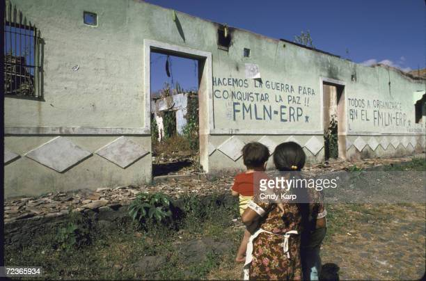 Local woman and child walk by FMLN-ERP griffiti-covered building that was destroying in the civil war, in northern Amazon region of El Salvador.