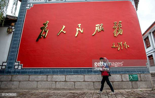 A local woman and her baby walks past a huge screen wall in front of local government on the wall writes five big Chinese characters service for the...