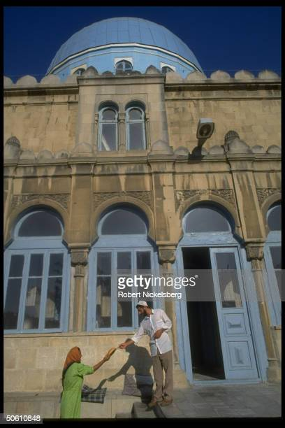 Local woman handing round loaf of bread to man poised outside mosque in Baku Azerbaijan