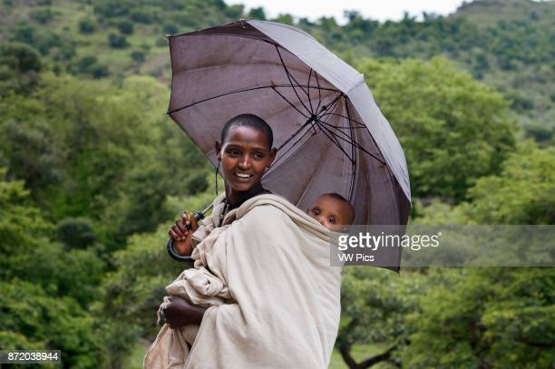 Local woman in Tis Isat or Blue Nile waterfalls Bahar Dar Ethiopia Africa Portrait of a mother next to her son at the foot of the Blue Nile Falls The...
