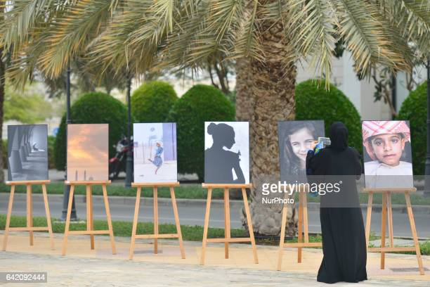 A local woman is taking a picture during an outdoor painting and photography exhibition at Sultan Qaboos University in Al Khoudh On Thursday February...