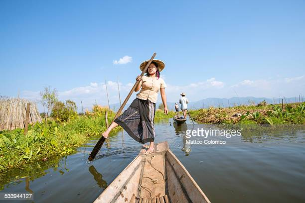 Local woman leg rowing wooden boat on river