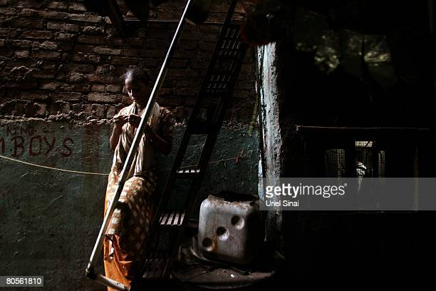 A local woman looks on at the entrance to her one room home at the Dharavi slum said to be 'Asia's largest slum' April 2008 in Mumbai India A city...