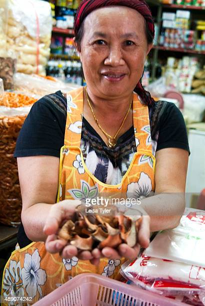 A local woman selling dried mushrooms on the market in Phuket Old Town Thailand built by Hokkien Chinese migrants locally known as Baba people and...