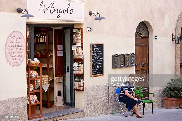 Local woman sitting outside L'Angolo delicatessen food shop in Montalcino Val D'OrciaTuscany Italy