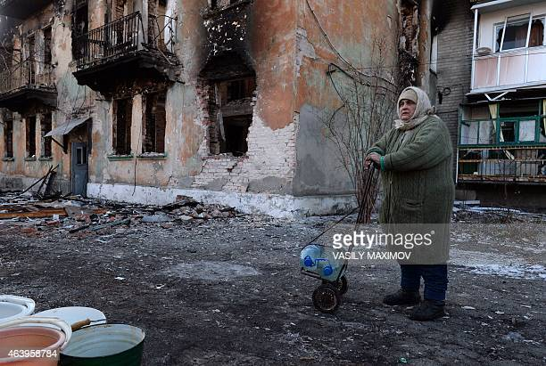 Local woman uses a shopping trolley to carry water containers past a damaged building in the eastern Ukrainian city of Debaltseve in the Donetsk...
