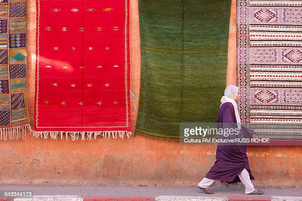 Local woman walking past hand crafted rugs, Marrakesh, Morocco