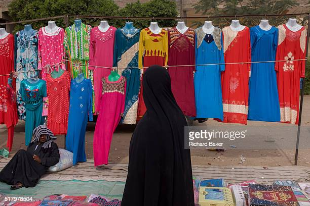 Local woman walks past colourful dress designs on a stall at the weekly market at Qurna, a village on the West Bank of Luxor, Nile Valley, Egypt. The...