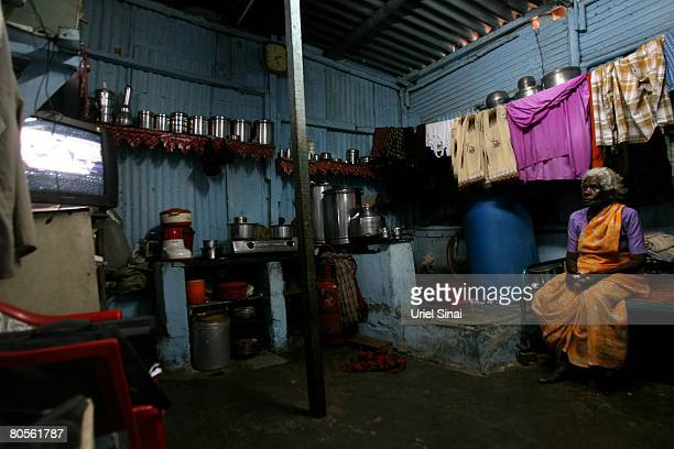 A local woman watches the television in her one room home at the Dharavi slum said to be 'Asia's largest slum' April 2008 in Mumbai India A city...