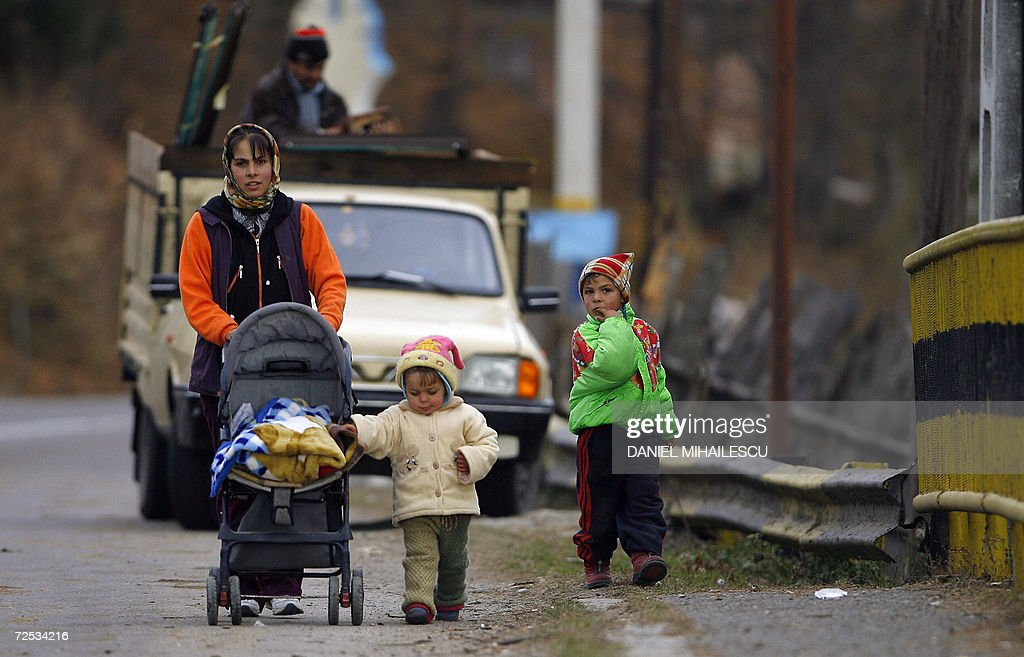 A local woman with her children enter the village of Glod