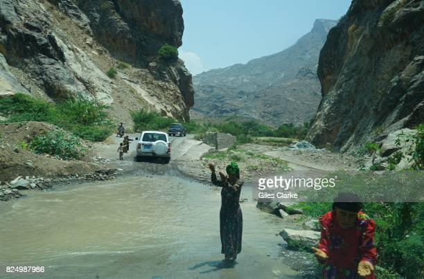 Local women beg on the side of a flooded rough road near Hajjah Yemen